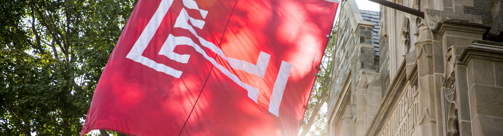 The sun peeks from behind a large red Temple University flag.