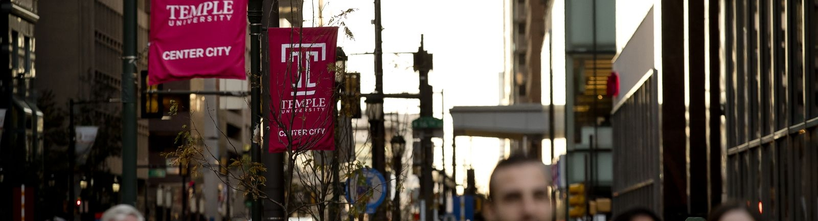 Temple University Center City banners hanging over a busy street in Center City Philadelphia