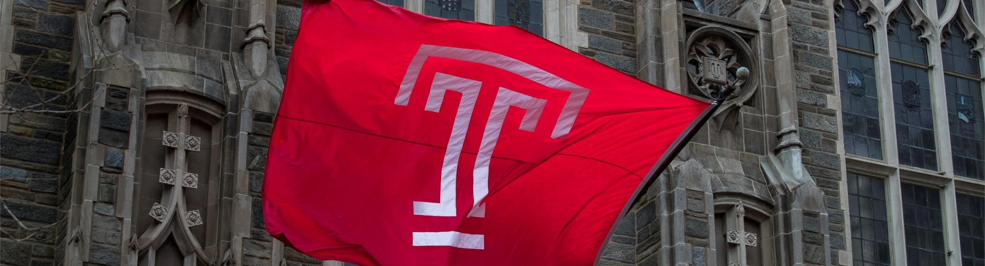 The Temple T flag raised in front of Mitten Hall.