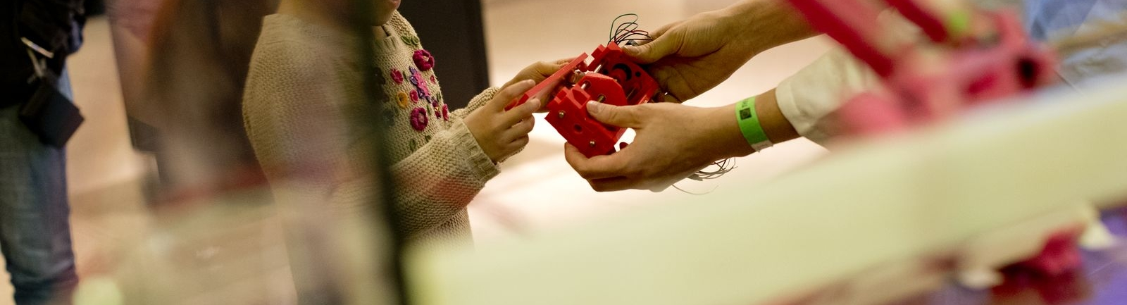 A Temple University professor shows a child a 3D-printed item.