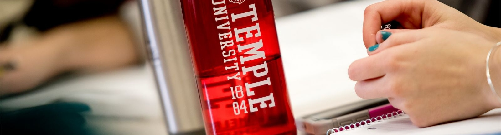 A Temple University water bottles sits atop a student's desk.
