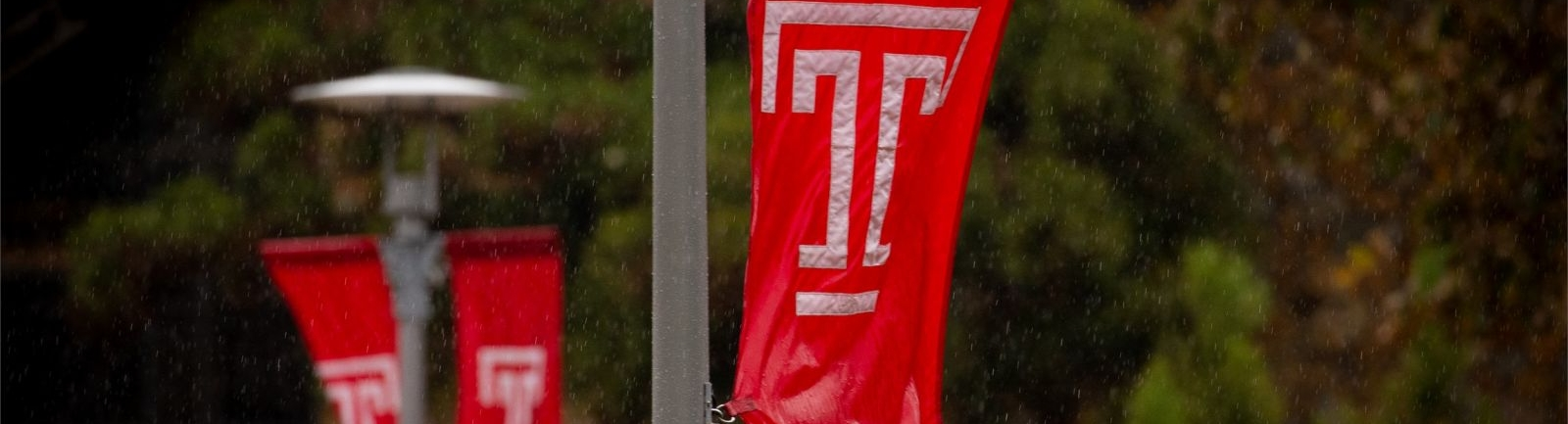 Temple University banners brave the wind and rain to provide school spirit.