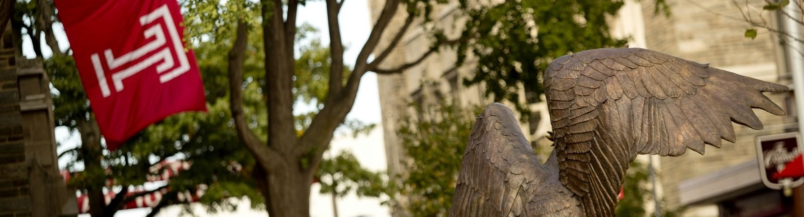 A Temple University flag flies just beyond a statue in Lenfest Circle.