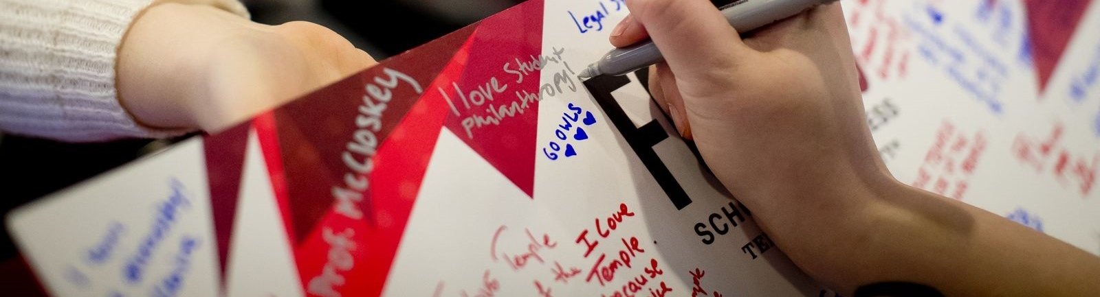 Temple University students and alumnus sign a card stating how much they enjoyed their college experience.