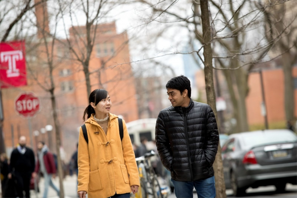 Two Temple University students walking together on campus in the winter.
