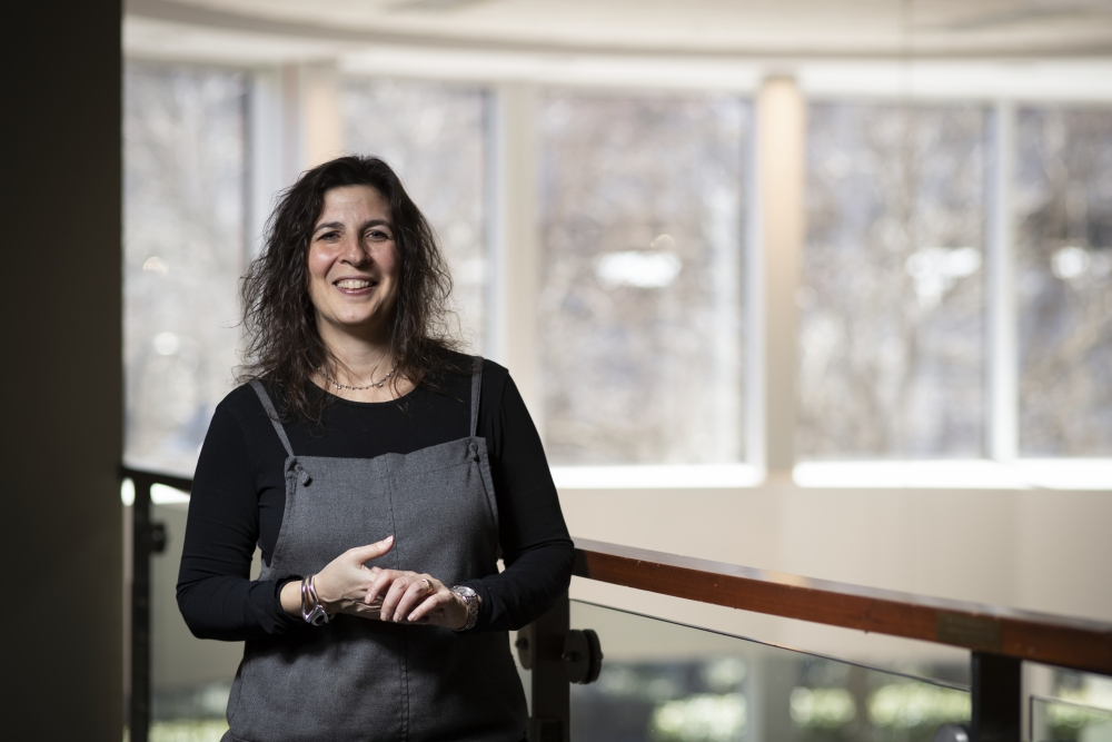 Dr. Suzie Mindel stands in front of windows smiling in an academic building at the Philadelphia College of Osteopathic Medicine.