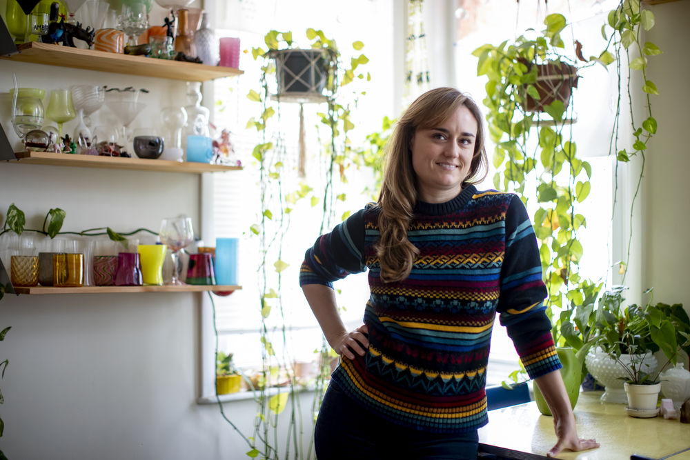 Glass artist Amber Cowan stands smiling in her bright kitchen surrounded by glass sculptures and hanging plants.