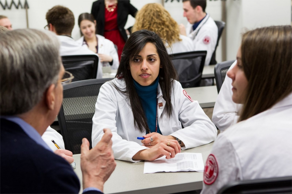 Students within Temple University's Lewis Katz School of Medicine work in small groups with a professor.