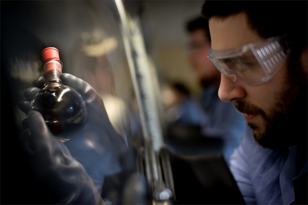 A Temple University student wearing safety goggles works carefully within the incubator lab.